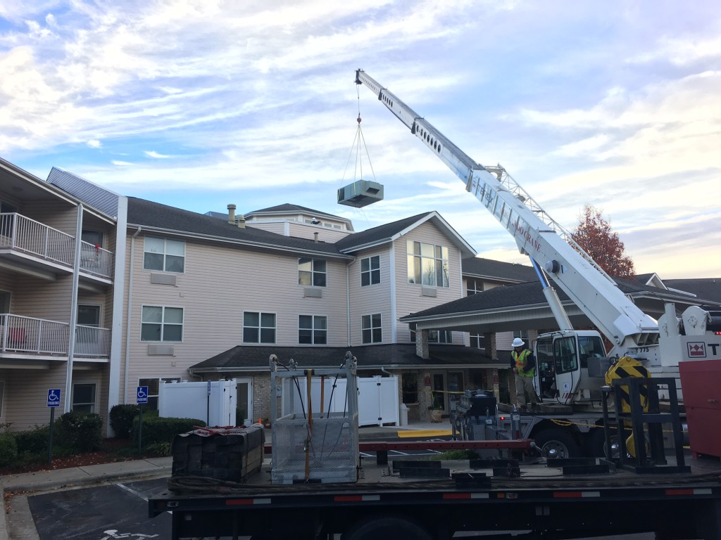 Crane raises old package unit off the roof of a retirement home in Durham North Carolina