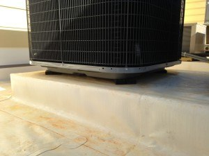 Vibration absorbing pads installed under a rooftop HVAC unit.